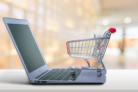 Laptop and shopping cart on beach background