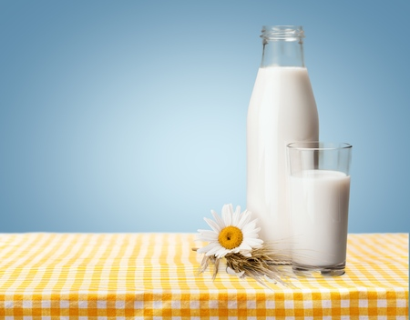 Pouring a glass of milk on a white wooden table on a blue background, tasty, nutritious and healthy dairy products Banque d'images