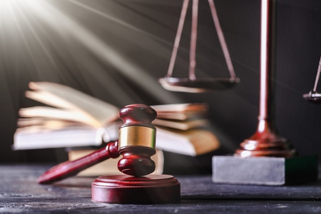 Justice Scales and books and gavel on wooden table