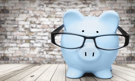 Piggy bank in glasses on wooden table