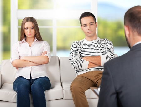 Upset couple sit on a sofa with arms crossed during a psychotherapy Standard-Bild