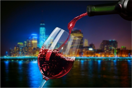 Red wine pouring in glass on blurred background Stock Photo