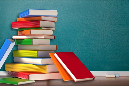 Stack of colorful books on wooden table