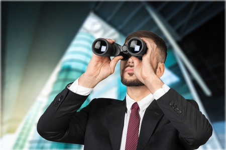 young businessman looking with binoculars