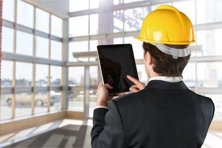 Young construction worker operating touch pad device Banque d'images