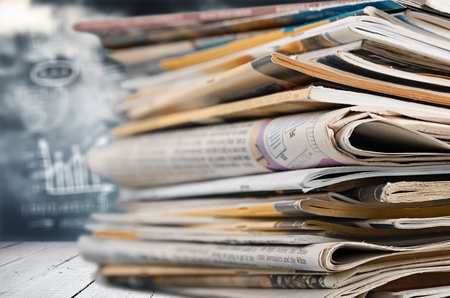 Newspapers folded and stacked on the table with garden or green background. Closeup newspaper and selective focus image. Time to read concept.