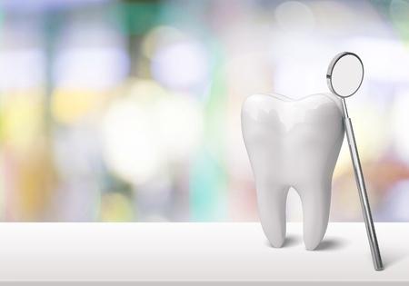 背景に歯科医院の大きな歯と歯科医の鏡