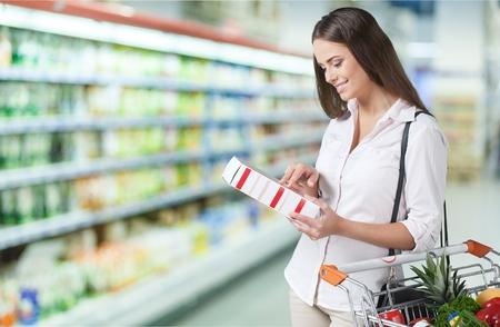Wijfje die voedsel etikettering in supermarkt controleren. Stockfoto - 90547883
