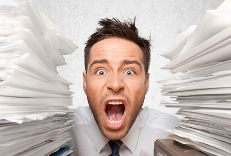 Wide-Eyed Office Worker Screams for Help btwn Folders