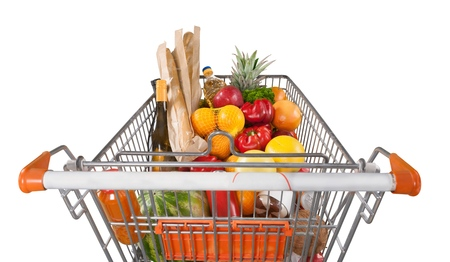 Shopping cart filled with various groceries in store