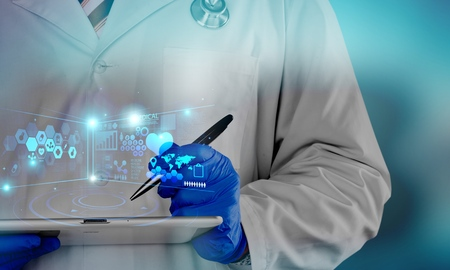 A physician, surgeon, examines a technological digital holographic plate represented the patients body, the heart lungs, muscles, bones. Concept: Futuristic medicine, world assistance, and the future