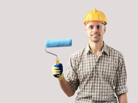 Funny man in an orange helmet with a brush Stock Photo