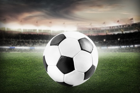 Football ball on stadium field background