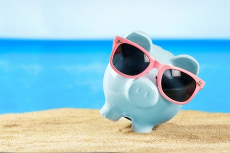 Piggy bank with sunglasses on sand beach Banco de Imagens