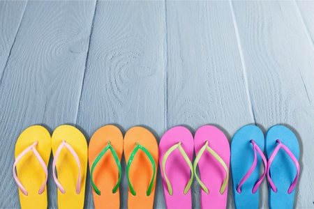 Rubber sandals flip flops on wooden background