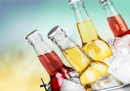 Beer bottles with ice on light background