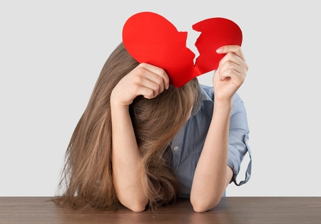 Beautiful brunette holding two parts of broken heart Standard-Bild