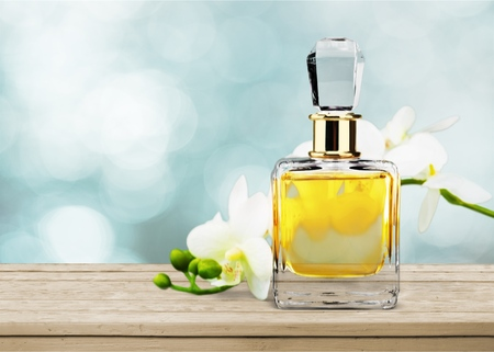 Perfume bottle and flowers on  background
