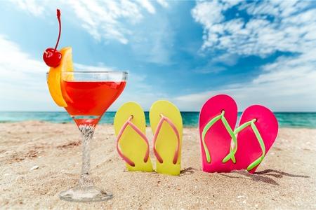 Row of colorful flip flops on beach against sunny sky Stock Photo
