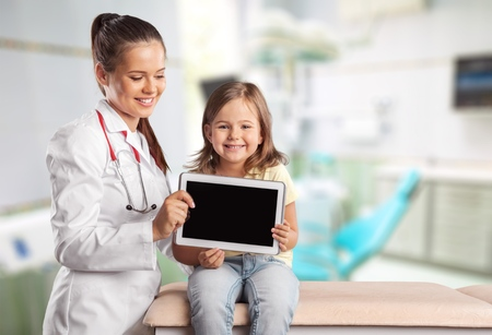 Young woman doctor with little girl  and tablet pc