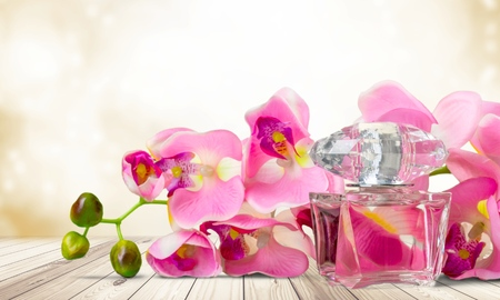 Perfume bottle and flowers on light background