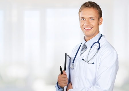 Handsome doctor with two nurses in the background Stock Photo