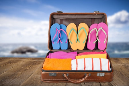 full travel suitcase with clothing and flip-flops Stock Photo