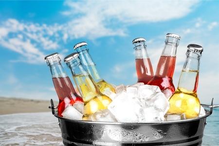 Beer bottles in ice on light background
