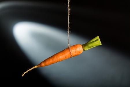 Carrot hanging on string on black background Zdjęcie Seryjne