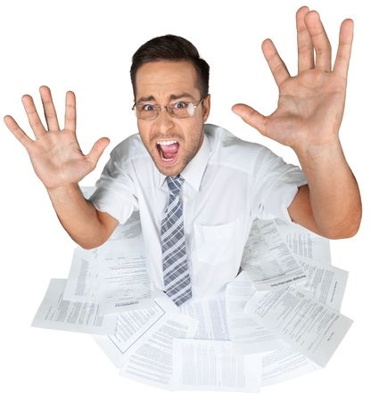 Portrait of businessman in glasses screaming in documents on white background