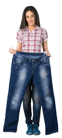 Young woman holding a pair of jeans that are way too big