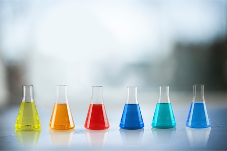 Open glass conical flasks standing in line with colorful liquids inside, chemical substances, solutions, standing on the white table in the laboratory 스톡 콘텐츠