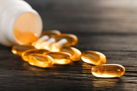 Fish oil capsules with omega 3 and vitamin D in a plastic bottle on a shiny texture with sun beams, healthy diet concept 写真素材