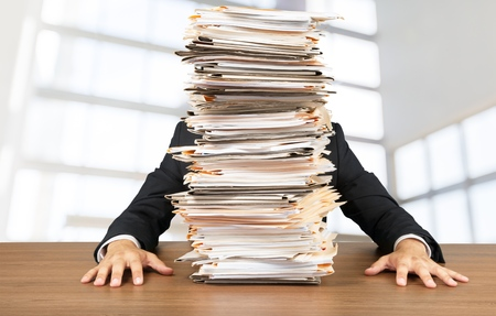 Young businessman with stack of papers Stock Photo