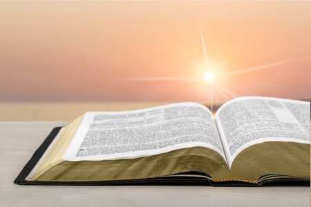 Detail of an old holy bible open with a beautiful and mystical sky in the background in a golden light