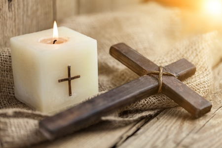 Closeup of wooden Christian cross on bible, burning candle on the old table. Church utensils.