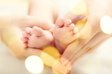 Baby feet in mother hands. Tiny Newborn Babys feet on female Heart Shaped hands closeup. Mom and her Child. Happy Family concept. Beautiful conceptual image of Maternity