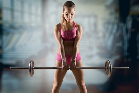 Fitness woman doing a weight training by lifting a heavy kettlebell