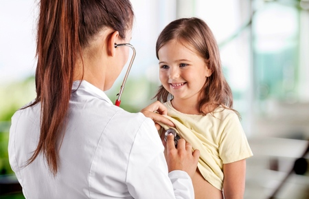 Female doctor listening the heart break of preschool girl. Doctor and her patient sitting at surgery. Stock Photo