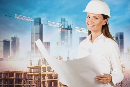Female architect at a construction site holding blueprints Stock Photo
