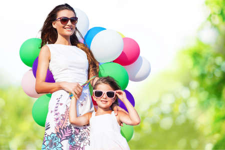 summer holidays, celebration, family, children and people concept - mother and child with colorful balloons Stock Photo