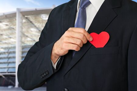 The elegant man in  suit hiding a red heart into pocket