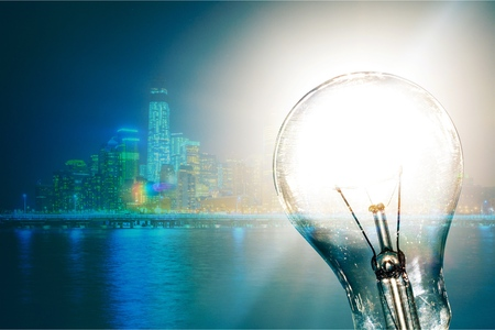Standard Incandescent Light Bulb on Blue Background 免版税图像