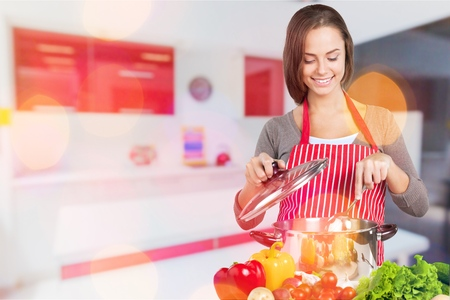 happy woman cooking at kitchen Stock Photo