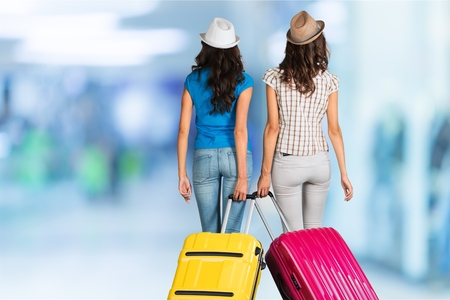 group of happy young tourist going on vacation bring suitcase viewed from behind