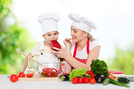 mother feeding kid daughter vegetables in kitchen Stock Photo