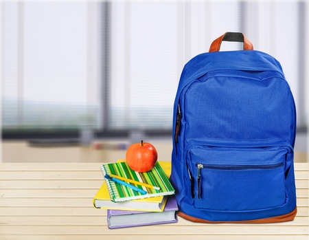 blue school backpack with stationery isolated on white background