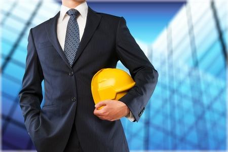 Ingeniero casco amarillo para la seguridad de los trabajadores en el fondo de un nuevo edificio de apartamentos de gran altura y grúas de construcción y cielo atardecer de noche Foto de archivo - 91807530