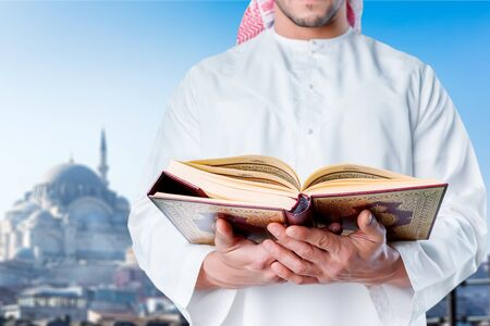 A senior cleric is portrayed with a book in his hands.