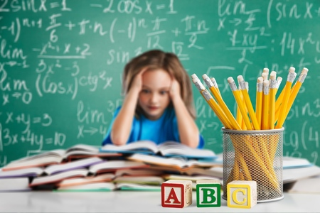 Thinking child bored in classroom